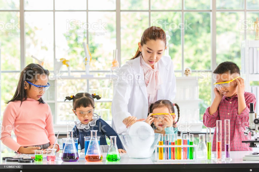 Science teacher teach Asian students about chemicals, colorful test...