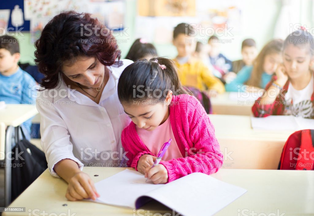 Teacher teaches to write to the girl student in the class