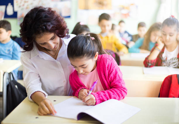 Teacher teaches to write to the girl student in the class stock photo