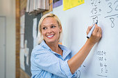 Teacher teaching how to count on whiteboard in classroom. Smiling blonde woman explaining additions in column in class. Math'u2019s teacher explaining arithmetic sums to elementary children.