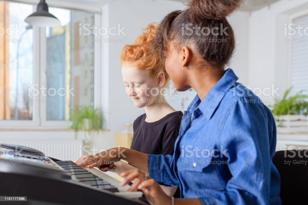 Teacher teaching piano to female student in class Mid adult teacher teaching piano to girl. Pre-adolescent student is learning music in training class. They are sitting at conservatory. 12-13 Years Stock Photo