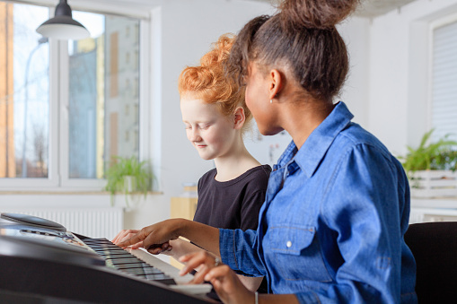 Teacher Teaching Piano To Female Student In Class Stock Photo - Download Image Now