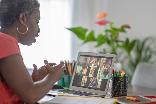 Female African American teacher teaching an online lesson to her students via video chat during the COVID-19 outbreak.