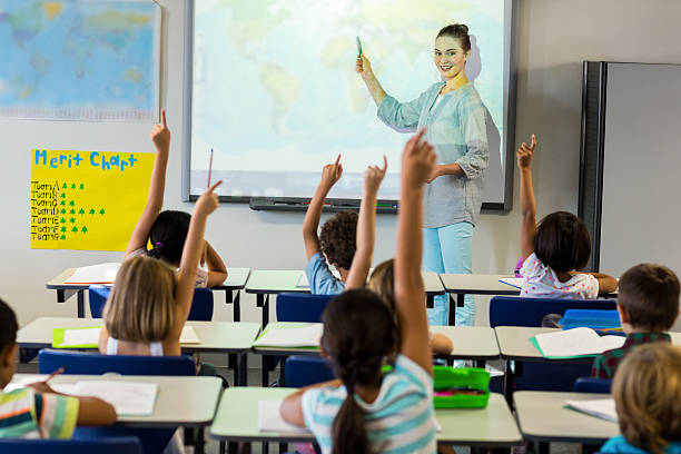 teacher teaching schoolchildren using projector screen - projection equipment stock pictures, royalty-free photos & images