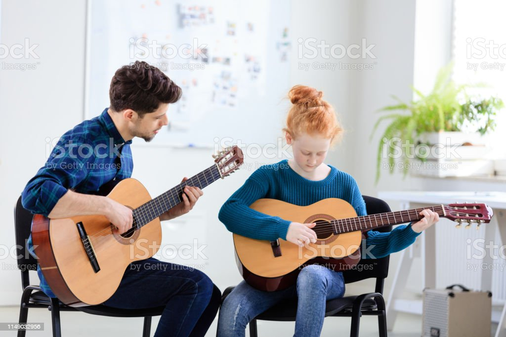 Teacher teaching student plucking guitar at class Male teacher teaching student plucking guitar at classroom. Girl is practicing string instrument at training class. They are in conservatory. 12-13 Years Stock Photo