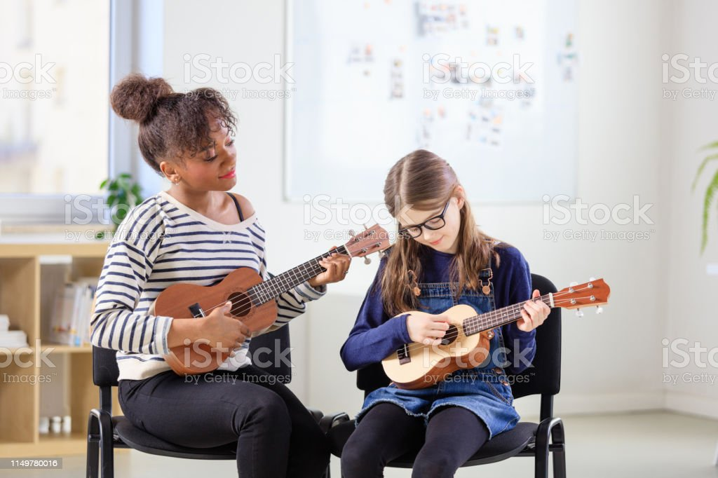 Teacher teaching student plucking ukulele in class Ukulele player looking at girl plucking string instrument at classroom. Multi-ethnic females are practicing music at training class. They are in conservatory. 10-11 Years Stock Photo
