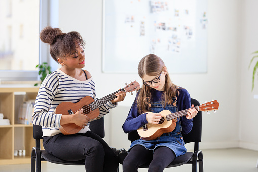 Teacher Teaching Student Plucking Ukulele In Class Stock Photo - Download Image Now