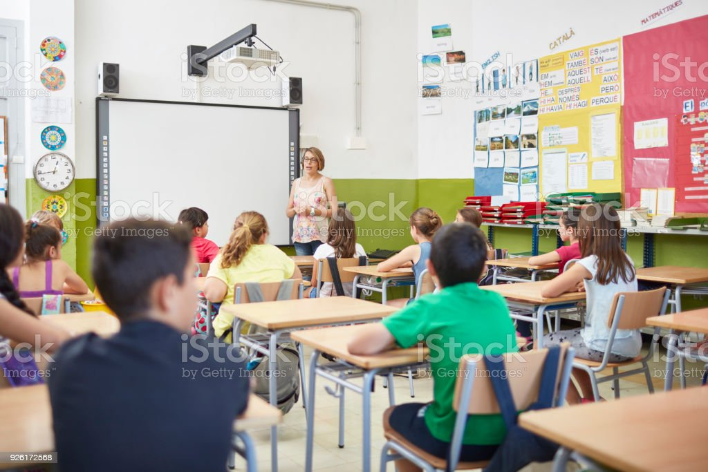 Teacher teaching students in classroom at school stock photo