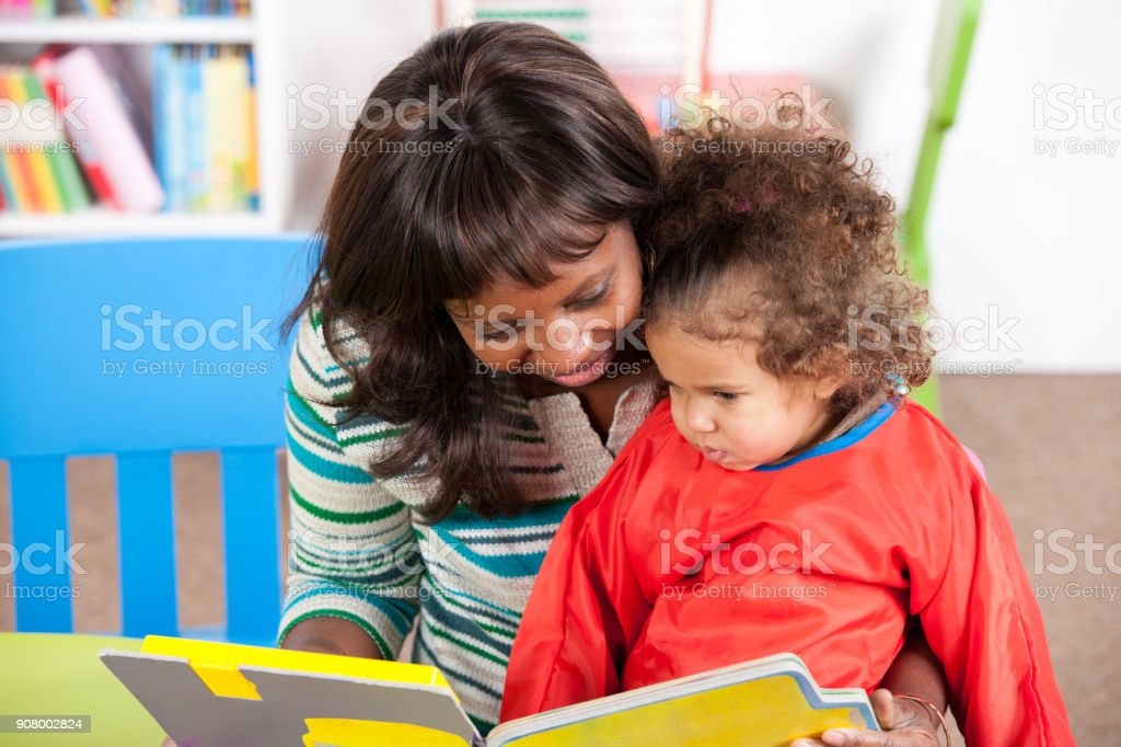 Teacher telling story from book to cute baby girl stock photo