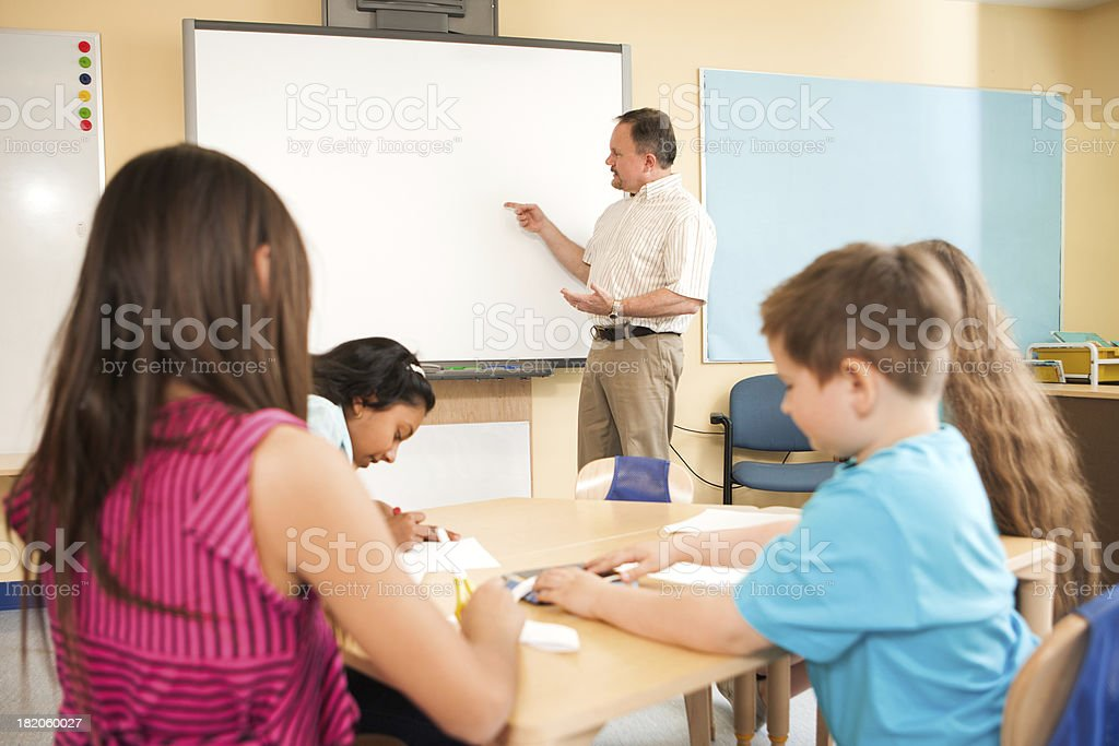 Teacher using an interactive whiteboard in a classroom stock photo