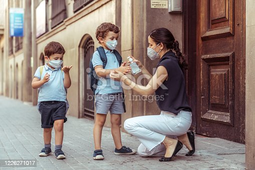istock Teacher using hand sanitizer with kids going back to school 1226271017