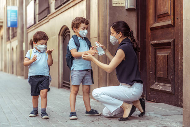 teacher using hand sanitizer with kids going back to school - social distancing stock pictures, royalty-free photos & images