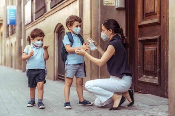 Lehrer mit Handdesinfektionsmittel mit Kindern, die zurück zur Schule gehen – Foto