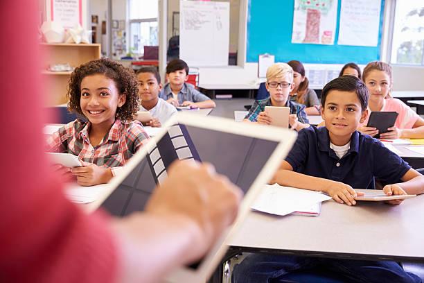 Professor, usando o Tablet na escola primária de aula - foto de acervo