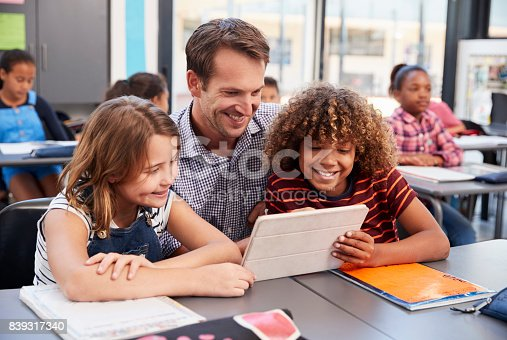 istock Teacher using tablet with two pupils in school class 839317340