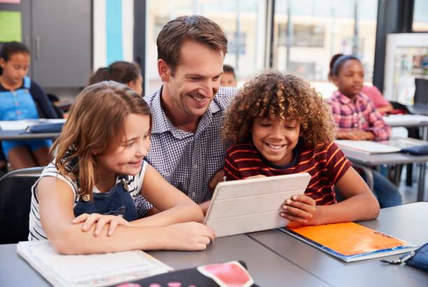 Professor, usando o tablet com dois alunos na classe de escola - foto de acervo