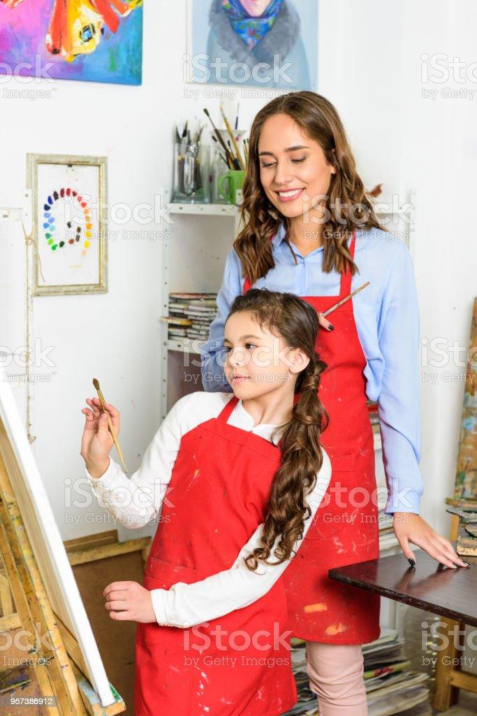 teacher watching how pupil painting in workshop of art school stock photo
