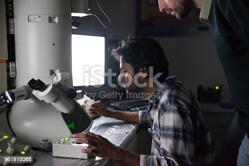 840623374 istock photo Teacher Watching Student Using Field Emission Electron Microscope 961915088