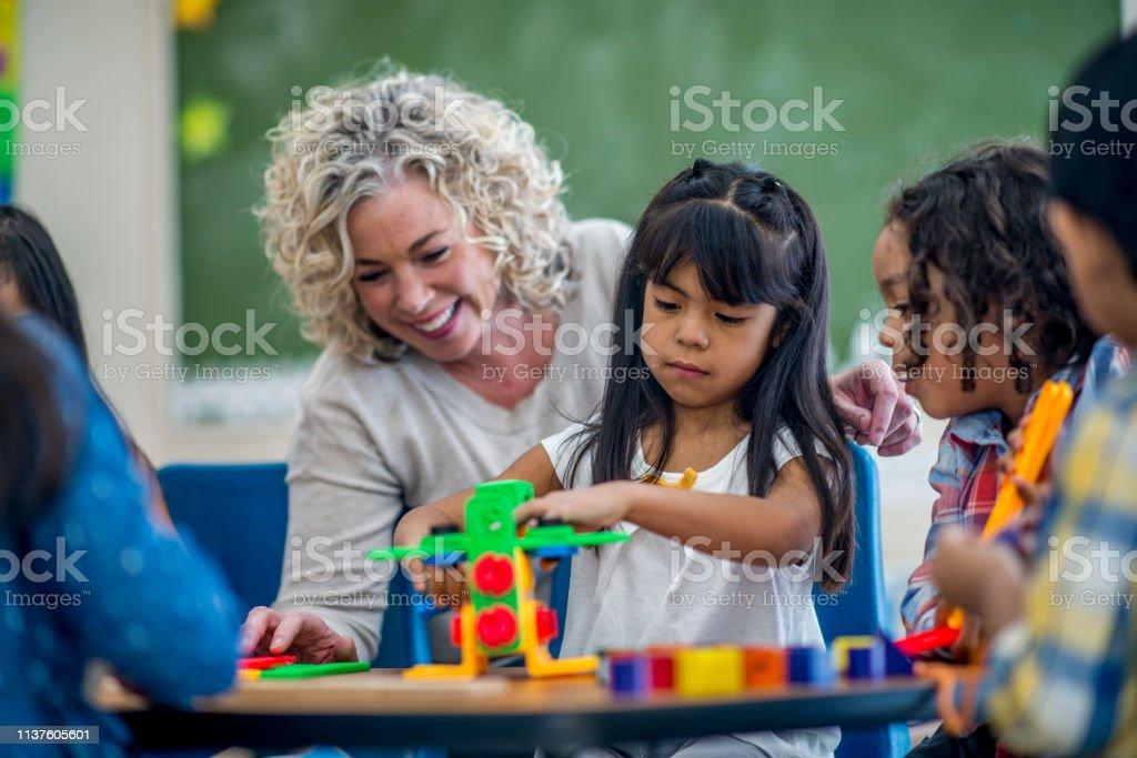 Group of children sitting with their teacher in their kindergarten...