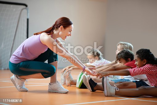 PE teacher smiling. PE teacher wearing leggings smiling while helping dark-skinned girl stretching