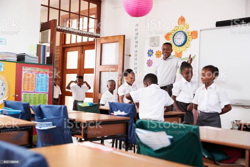 Profesor da la bienvenida a los niños al llegar a clase de la escuela primaria - foto de stock