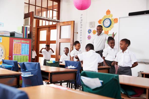 profesor da la bienvenida a los niños al llegar a clase de la escuela primaria - regreso a clases fotografías e imágenes de stock