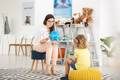 istock Teacher with blue ball and kind kid in the classroom with toys 1044803728