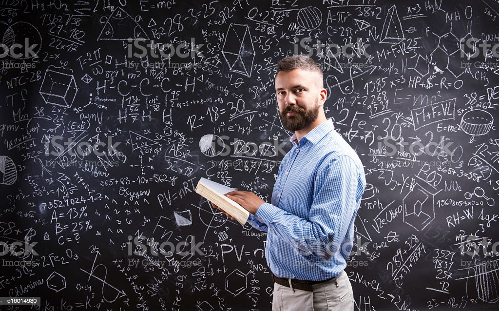 Teacher With Book Against Big Blackboard With Symbols And Formul