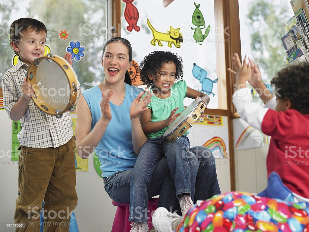 Teacher With Children Playing Music In Class stock photo