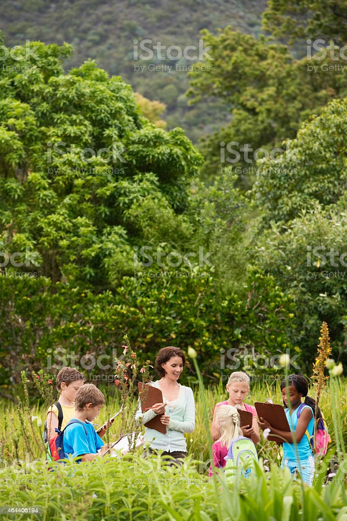 Teacher With Children Preparing Notes During Field Trip stock photo
