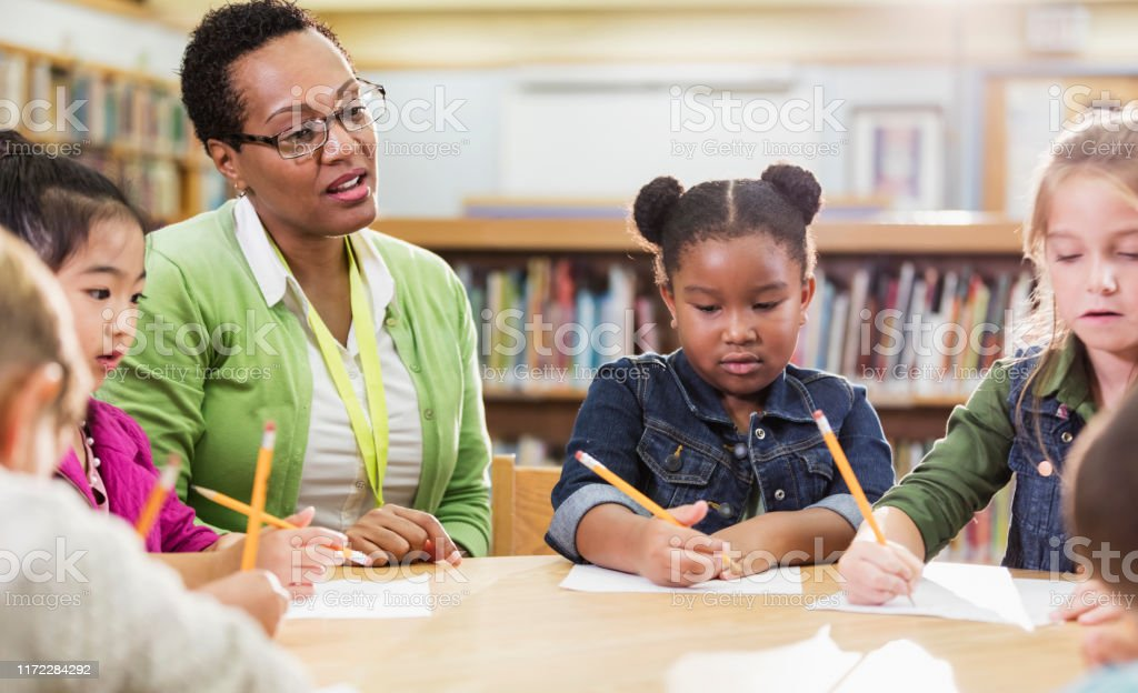 Teacher with children sitting at table, writing An African-American teacher sitting at a round table in an elementary school library with a group of students, who are writing on paper with pencils. 45-49 Years Stock Photo