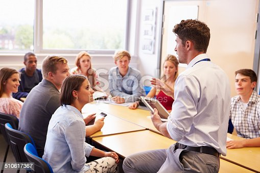 istock Teacher With College Students Giving Lesson In Classroom 510617367