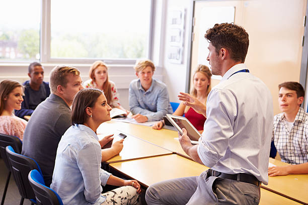 Teacher With College Students Giving Lesson In Classroom stock photo