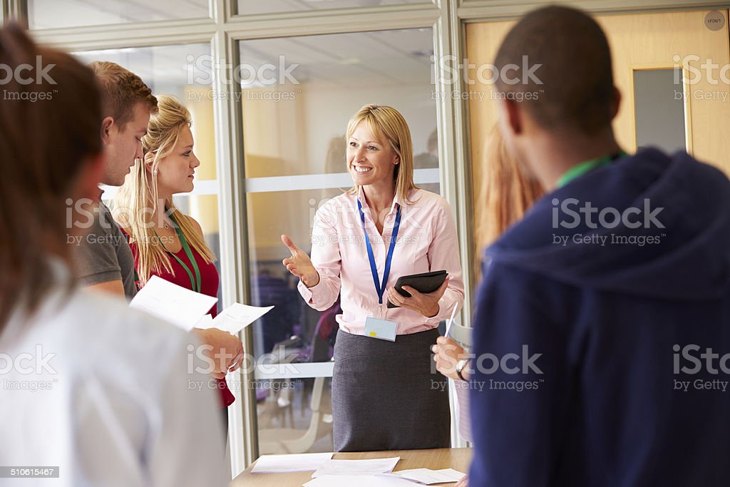 Teacher With College Students Standing By Desks In Classroom royalty-free stock photo