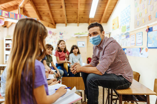 Teacher with face mask motivating kids to be active in classroom after coronavirus stock photo