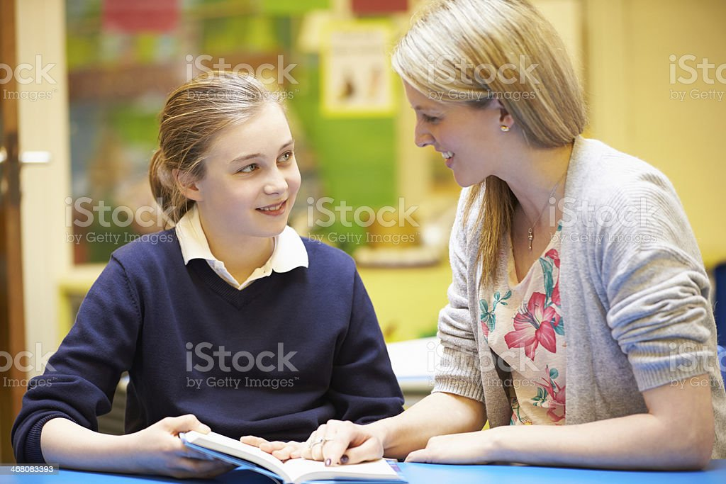 Teacher With Female Pupil Reading At Desk In Classroom stock photo