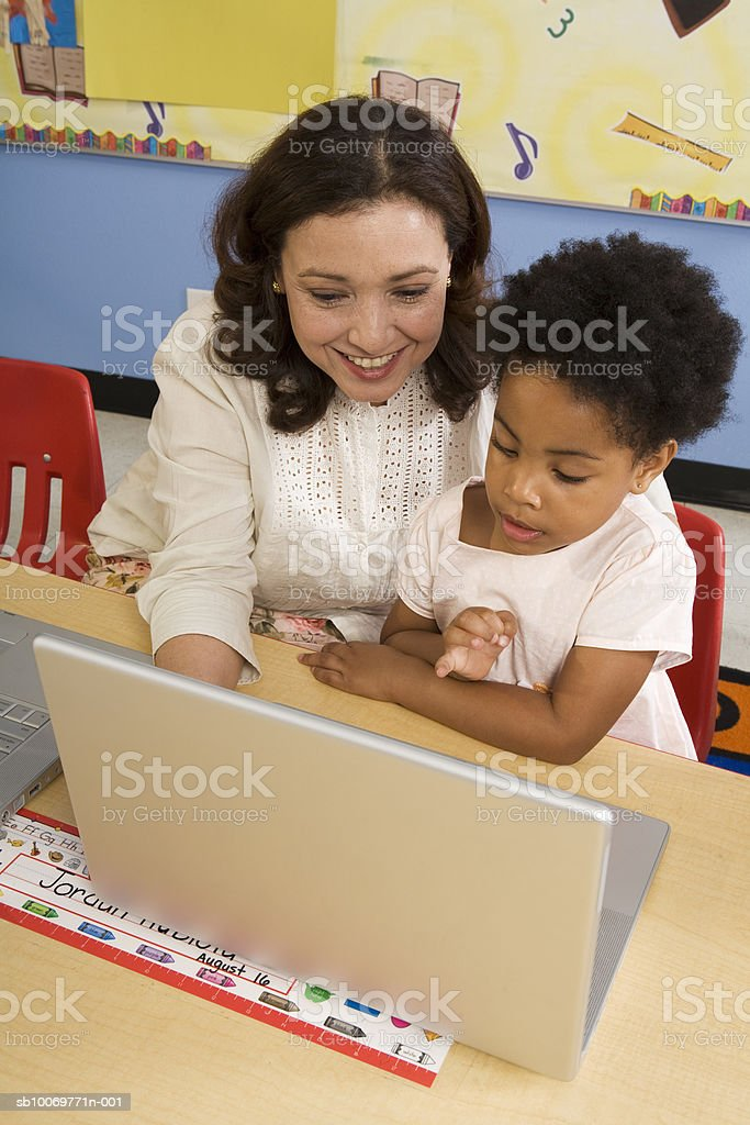 Teacher with girl (4-5) using laptop foto de stock libre de derechos