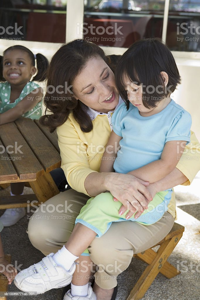 Teacher with girls (2-5) in garden, smiling 免版稅 stock photo