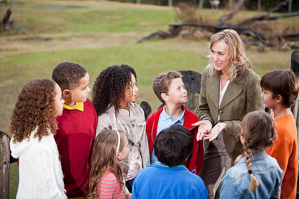Teacher with group of children at zoo Teacher (50s) with multi-ethnic group of elementary school children at zoo, standing on observation deck overlooking animal exhibit. field trip stock pictures, royalty-free photos & images