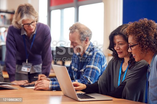 877026364 istock photo Teacher With Group Of Mature Adult Students In Class Sit Around Table And Work In College Library 1219860622