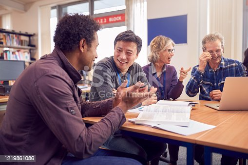 877026364 istock photo Teacher With Group Of Mature Adult Students In Class Sit Around Table And Work In College Library 1219861086