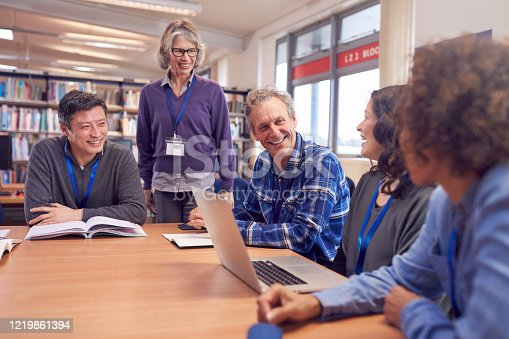 877026364 istock photo Teacher With Group Of Mature Adult Students In Class Sit Around Table And Work In College Library 1219861394