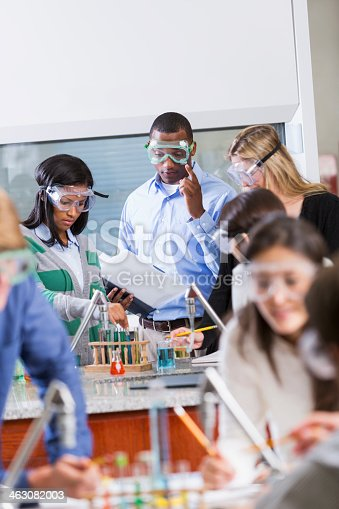 129300487 istock photo Teacher with group of students in chemistry class 463082003