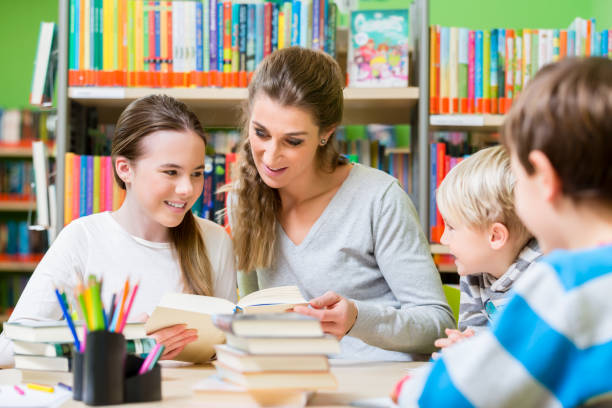Lehrer mit ihrer Klasse besuchen die Bibliothek Bücher zu lesen – Foto