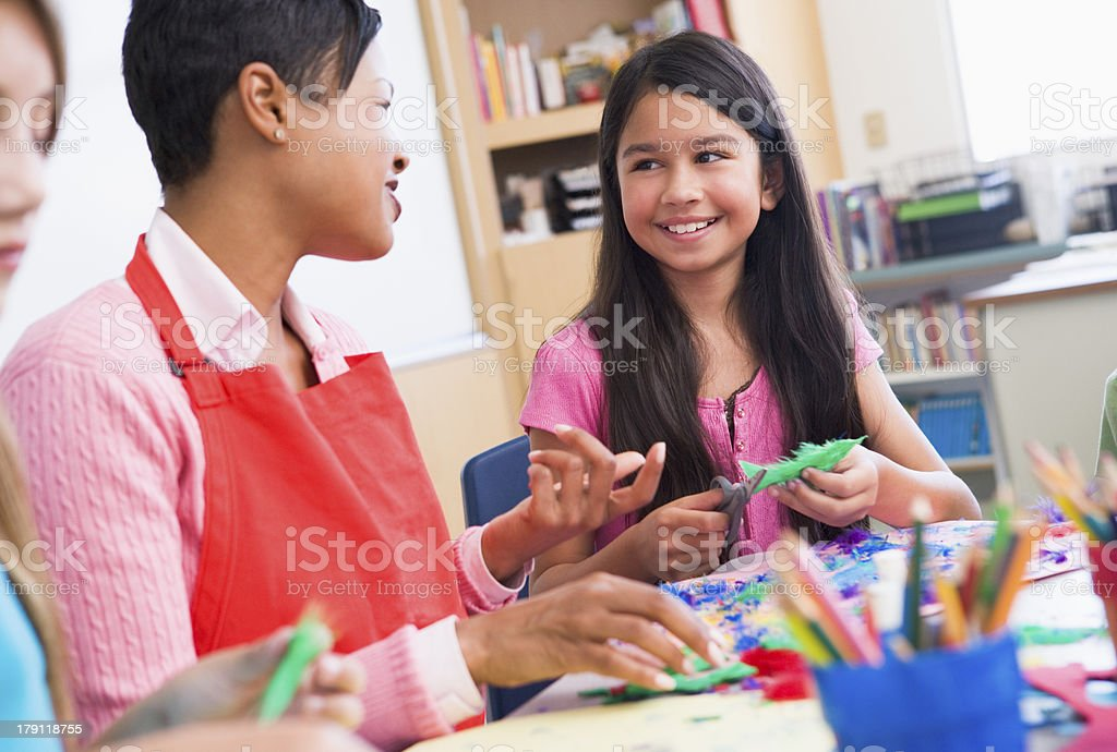 A teacher with her student in art class doing crafts stock photo