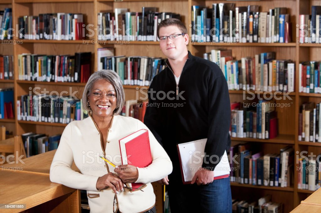 Teacher with high school student in library royalty-free stock photo
