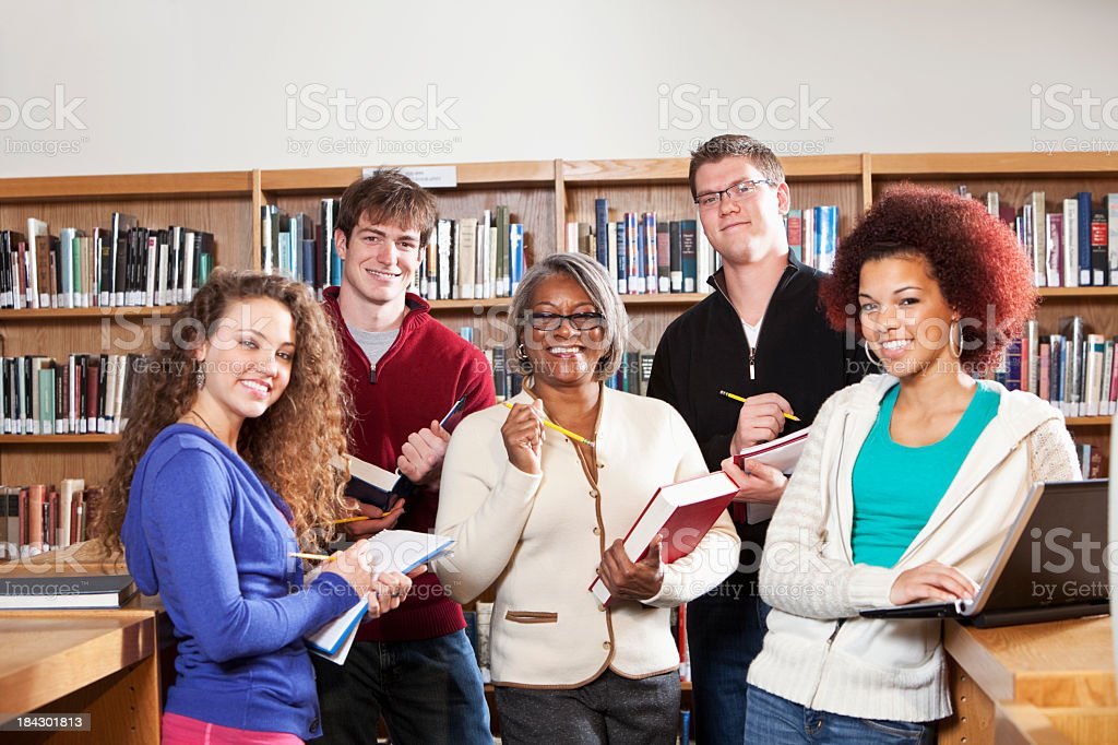 Teacher with high school students in library royalty-free stock photo