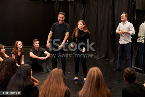 Teacher With Male And Female Drama Students At Performing Arts School In Studio Improvisation Class
