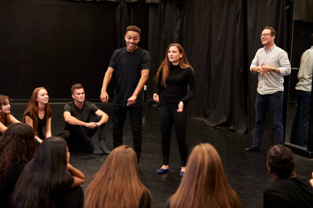 Teacher With Male And Female Drama Students At Performing Arts School In Studio Improvisation Class Teacher With Male And Female Drama Students At Performing Arts School In Studio Improvisation Class theatrical performance stock pictures, royalty-free photos & images