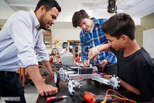 istock Teacher With Male Pupils Building Robotic Vehicle In Science Lesson 999232412